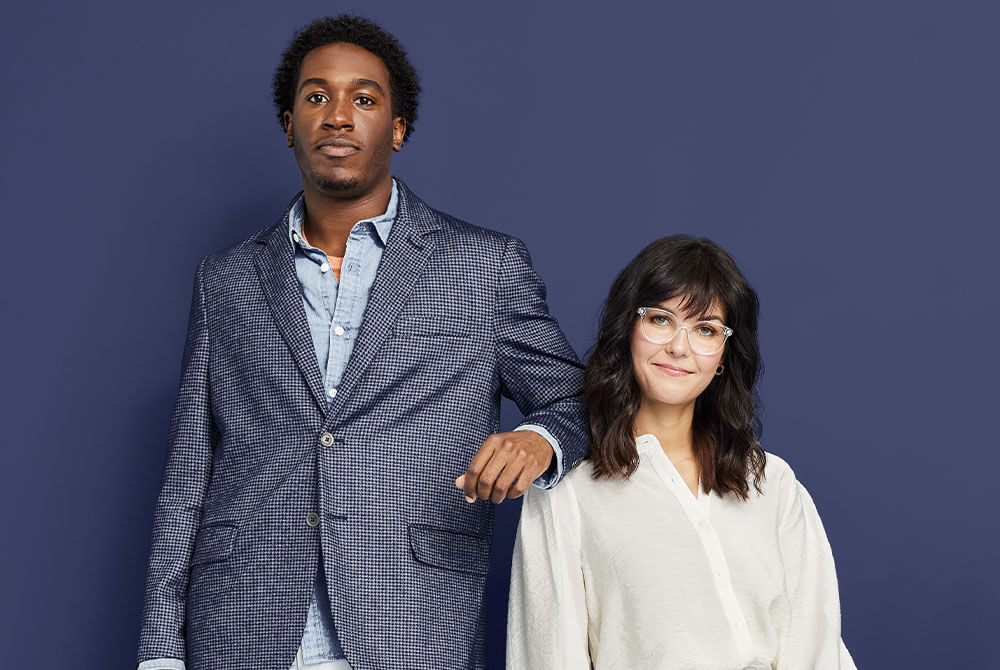 Man and woman dressed professionally facing the camera