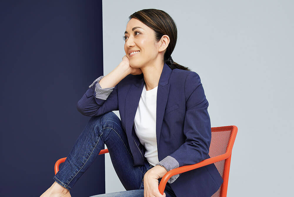Woman sitting on red chair and looking off to the right