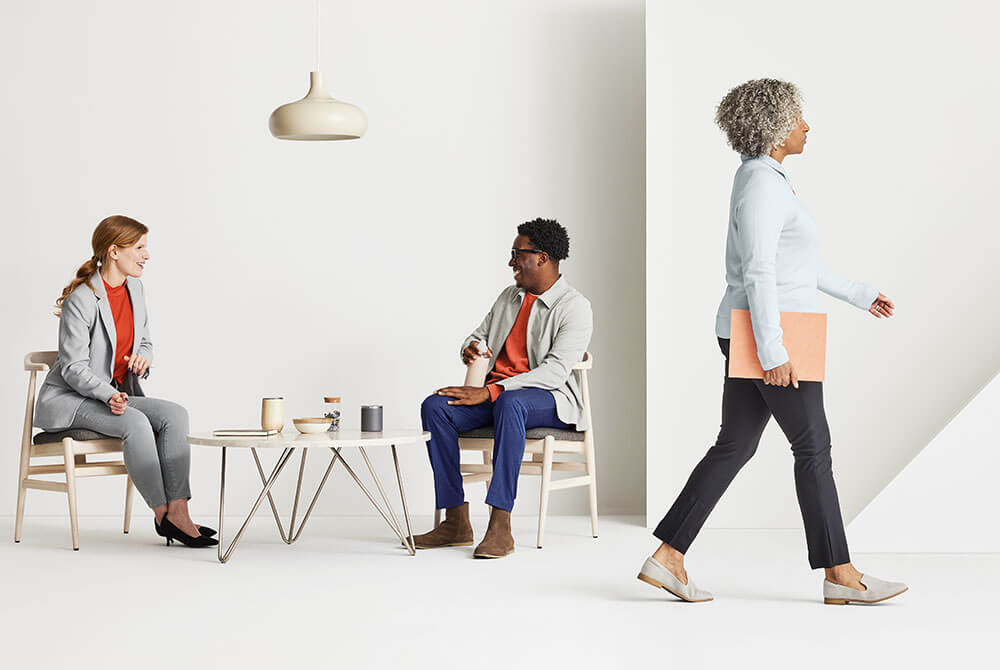 Two people sitting and talking and a woman walking past them holding folder