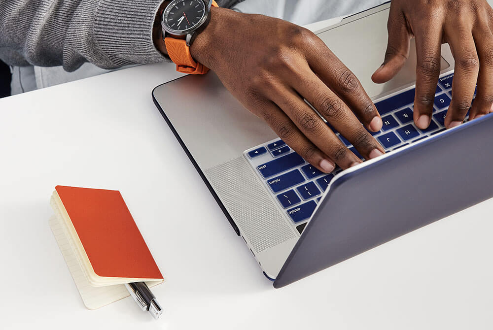 Image of hands working on computer and red notebook
