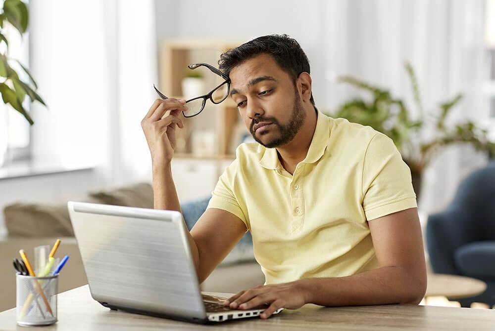 TIred man looking at his computer