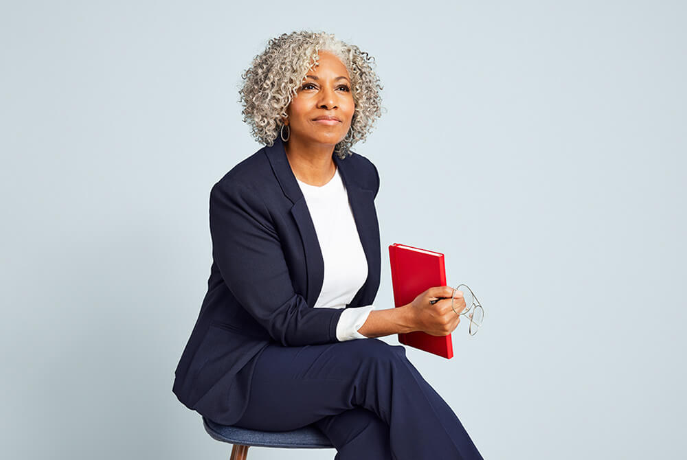 Woman sitting on chair holding glasses and a red book