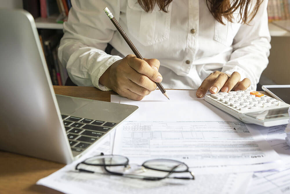 Woman working on budget with computer and calculator