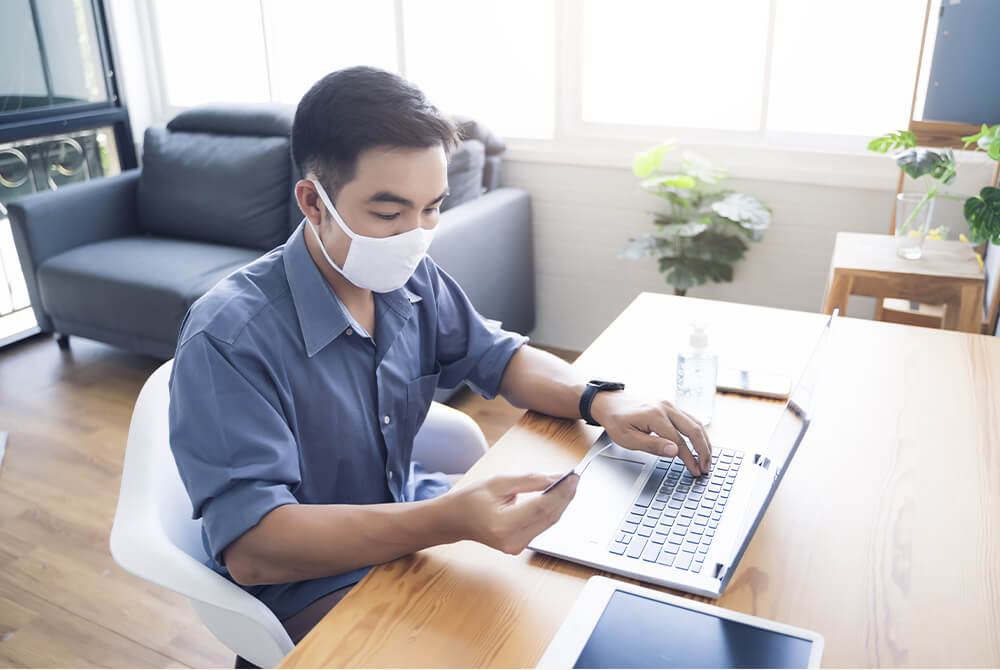 Guy wearing a facemask and working on the computer