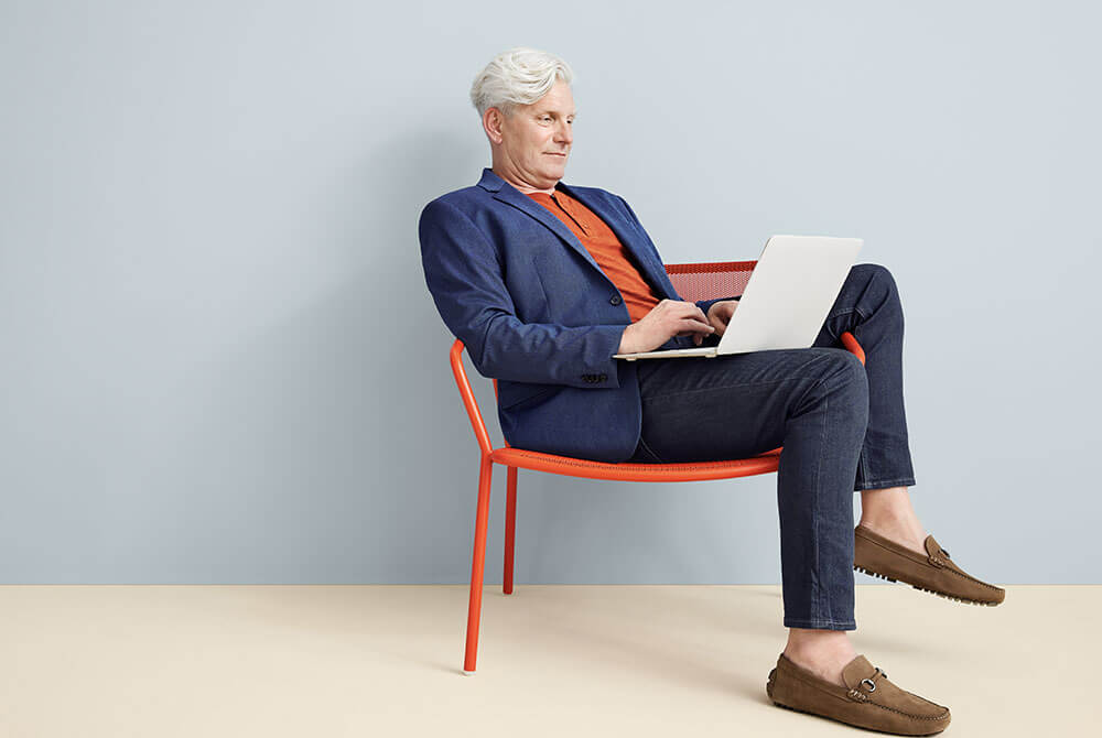 Man sitting in red chair working on computer
