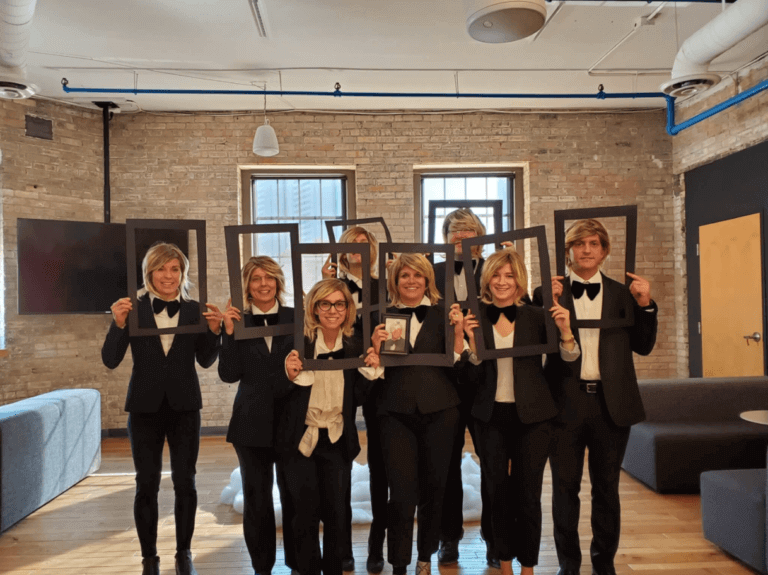 Salo employees dressed in tuxedos with black paper frames around their faces
