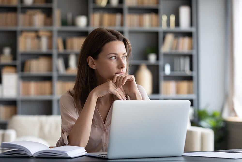 Woman working on computer and gazing off in thought