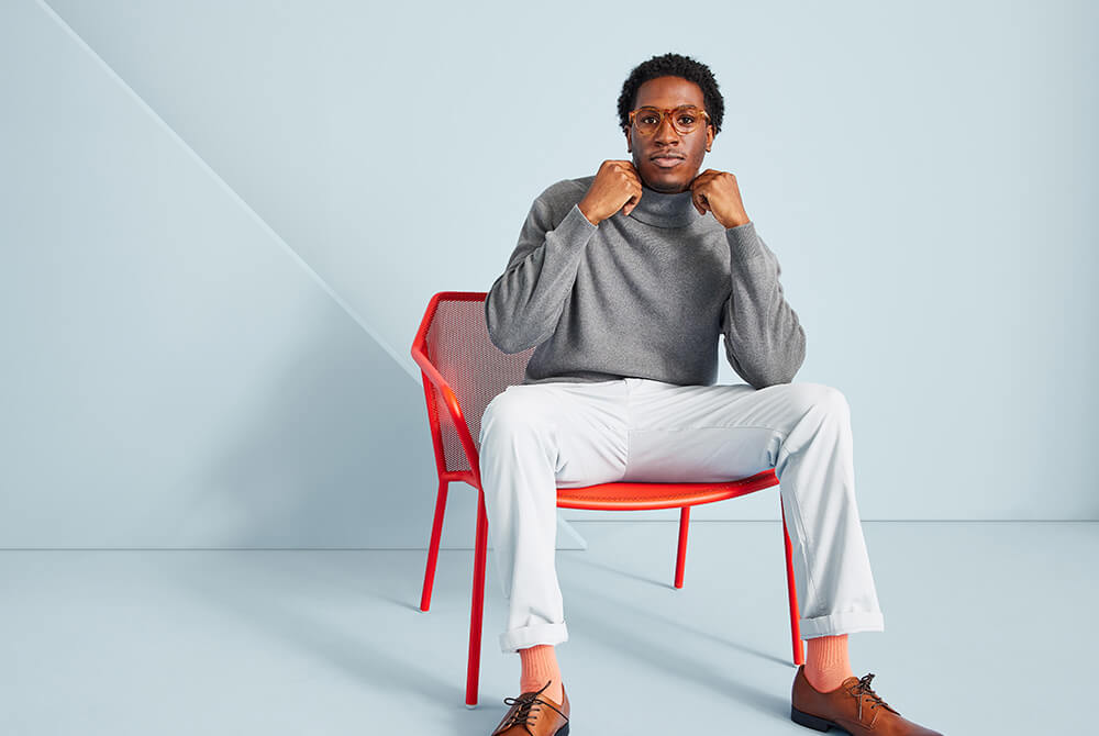 Man sitting on a red chair fixing his shirt