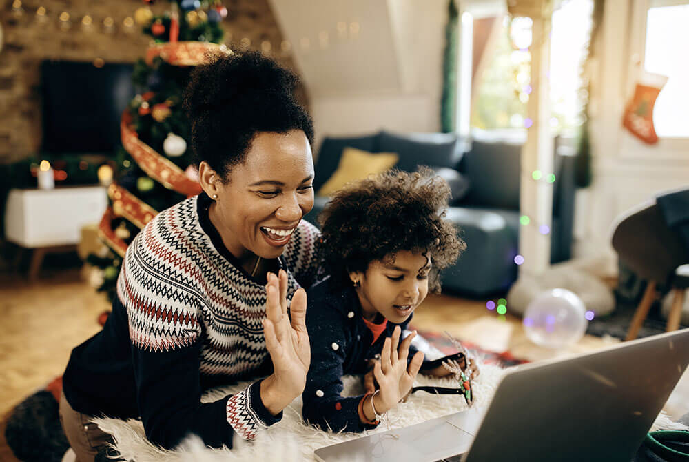 Woman and daughter dressed festively waving hello to the computer