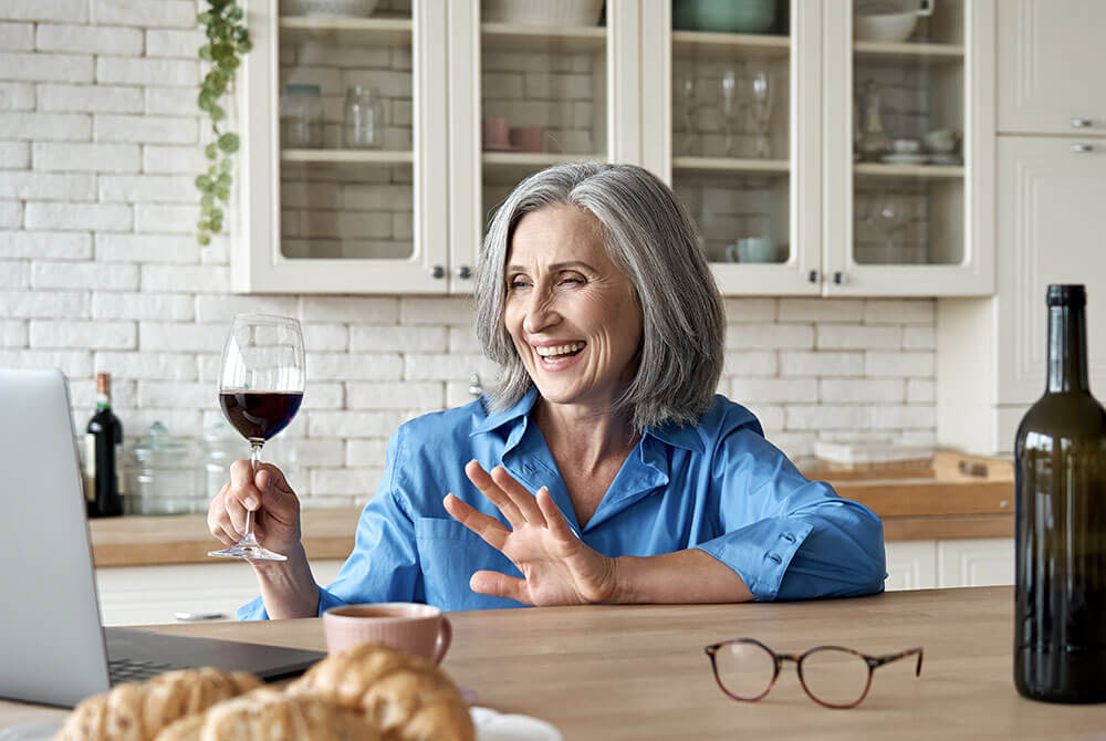 Woman with glass of wine waving hello to computer